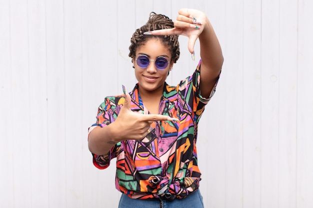 Jonge afro-vrouw die zich gelukkig, vriendelijk en positief voelt, lacht en een portret of fotolijst met handen maakt