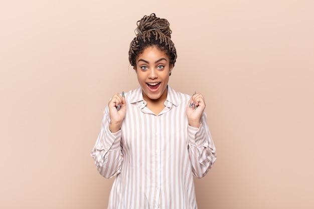 Jonge afro-vrouw die zich geschokt, opgewonden en gelukkig voelt, lacht en succes viert, zeggend wow!