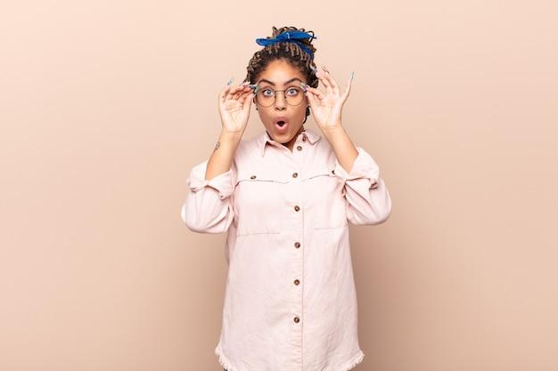 Jonge afro-vrouw die zich geschokt, verbaasd en verrast voelt, een bril vasthoudt met een verbaasde, ongelovige blik