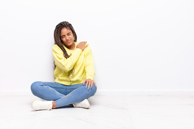 Jonge afro-vrouw die zich moe, gestrest, angstig, gefrustreerd en depressief voelt, rug- of nekpijn heeft