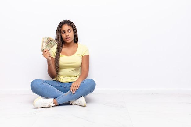 Jonge afro vrouw die zich verbaasd en verward voelt, haar hoofd krabt en naar de zijkant kijkt. geld concept