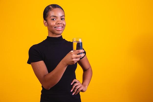 Jonge afro vrouw drinkwater op gele achtergrond. jong meisje met glas water