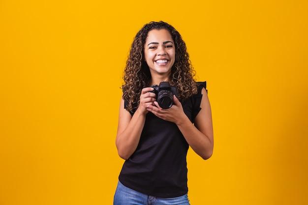 Jonge afro vrouw fotografie op gele achtergrond met een fotocamera.