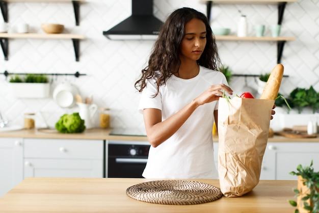 Jonge afro-vrouw gaat producten uit een papieren zak uitpakken