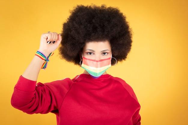 Jonge afro-vrouw gay pride-vlag, lesbienne en regenboogarmband, opgeheven vuist, lgbt-rechten