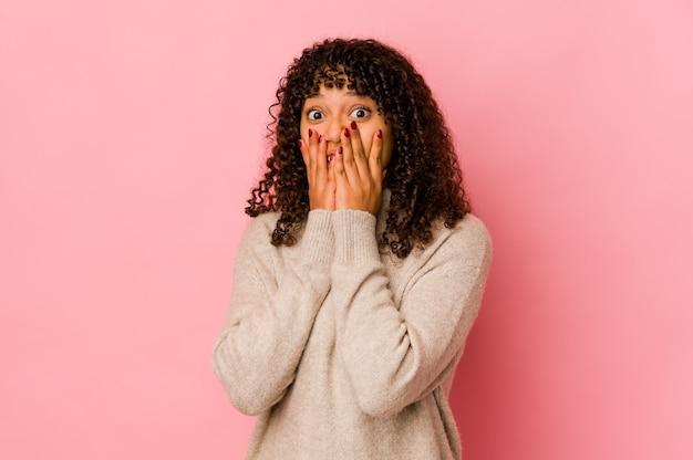Jonge afro-vrouw geïsoleerd geschokt, mond bedekt met handen, verlangend om iets nieuws te ontdekken
