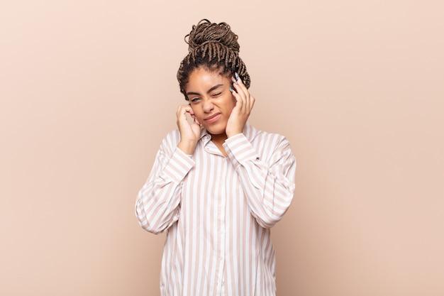 Jonge afro-vrouw kijkt boos, gestrest en geïrriteerd, beide oren bedekt met een oorverdovend geluid, geluid of luide muziek