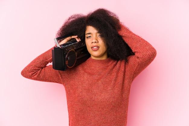 Jonge afro-vrouw met een geïsoleerde cassete die geschokt is, heeft ze een belangrijke vergadering onthouden.