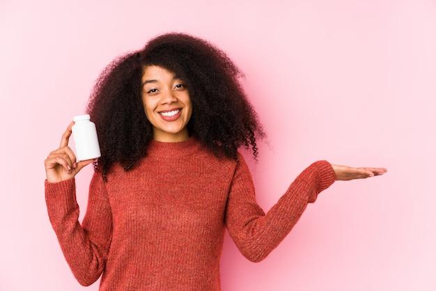 Jonge afro vrouw met een geïsoleerde vitaminen jonge afro vrouw met een vitaminsshowing een kopie ruimte op een palm en een andere hand op taille te houden.