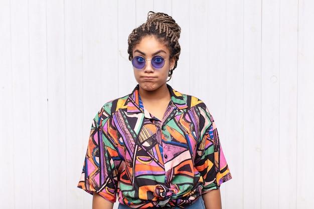 Jonge afro-vrouw met een gekke, gekke, verbaasde uitdrukking, puffende wangen, een vol gevoel