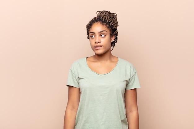 Jonge afro-vrouw twijfelt of denkt, bijt op lip en voelt zich onzeker en nerveus, op zoek naar ruimte aan de zijkant