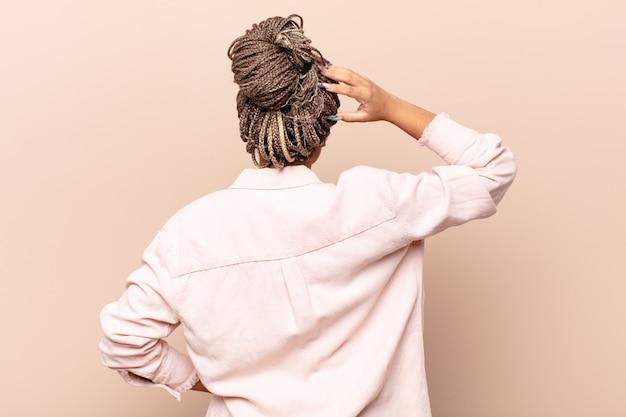 Jonge afro-vrouw voelt zich geen idee en verward, denkt een oplossing, met de hand op de heup en de andere op het hoofd