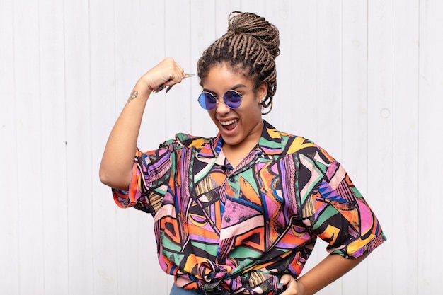 Jonge afro-vrouw voelt zich gelukkig, tevreden en krachtig, buigt fit en gespierde biceps, ziet er sterk uit voor de sportschool