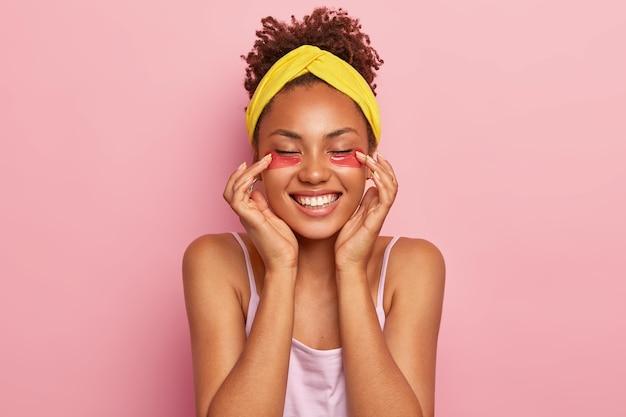 Jonge afro vrouwelijke model past collageen kussentjes toe onder de ogen, geniet van een hydraterende behandeling, glimlacht breed, toont witte tanden heeft frisse gezonde huid draagt gele hoofdband