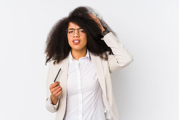 Jonge afro zakelijke vrouw met een credit car geïsoleerd jonge afro zakelijke vrouw met een credit carbeing geschokt, ze heeft belangrijke vergadering onthouden.
