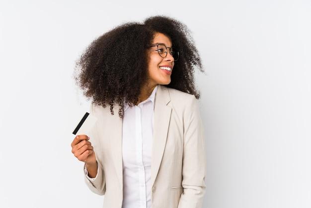 Jonge afro zaken vrouw met een krediet auto geïsoleerd jonge afro zaken vrouw met een krediet auto kijkt opzij glimlachen, vrolijk en aangenaam.