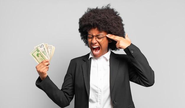 Jonge afro zakenvrouw die er ongelukkig en gestrest uitziet, zelfmoordgebaar maakt een pistoolteken met de hand, wijzend naar het hoofd. bedrijfsconcept