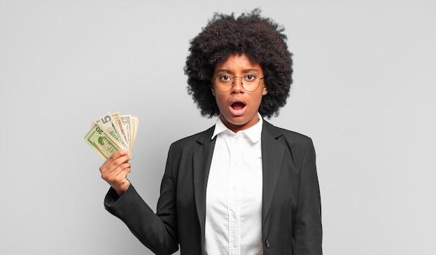 Jonge afro zakenvrouw die erg geschokt of verrast kijkt, starend met open mond en zegt wow. bedrijfsconcept