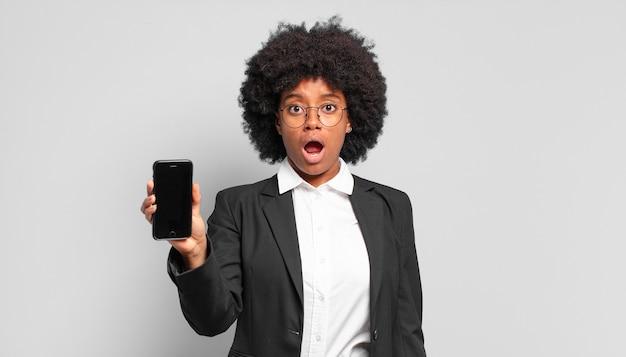 Jonge afro-zakenvrouw die erg geschokt of verrast kijkt, starend met open mond en zegt wow