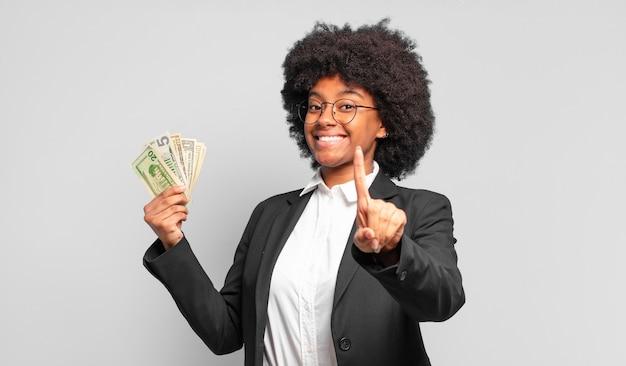 Jonge afro-zakenvrouw die trots en zelfverzekerd glimlacht en nummer één triomfantelijk laat poseren, zich een leider voelt. bedrijfsconcept