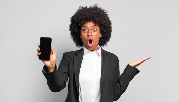 Jonge afro-zakenvrouw die verbaasd en geschokt kijkt, met open mond een voorwerp vasthoudt met een open hand op de zijkant.