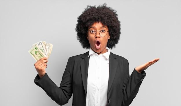 Jonge afro-zakenvrouw die verbaasd en geschokt kijkt, met open mond een voorwerp vasthoudt met een open hand op de zijkant