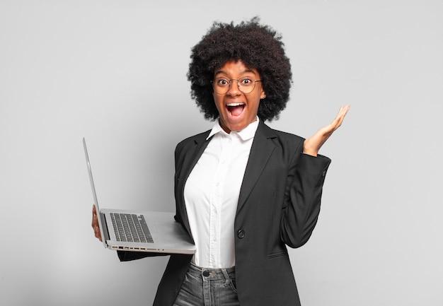 Jonge afro-zakenvrouw die zich blij, opgewonden, verrast of geschokt voelt, glimlacht en verbaasd is over iets ongelooflijks. bedrijfsconcept