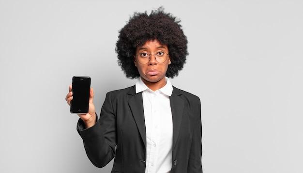 Jonge afro-zakenvrouw die zich verdrietig en zeurderig voelt met een ongelukkige blik, huilend met een negatieve en gefrustreerde houding. bedrijfsconcept