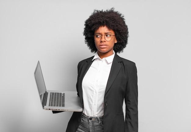 Jonge afro-zakenvrouw die zich verdrietig, overstuur of boos voelt en opzij kijkt met een negatieve houding, fronsend in onenigheid. bedrijfsconcept