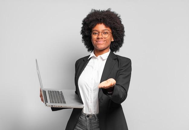 Jonge afro zakenvrouw glimlachend gelukkig met vriendelijke, zelfverzekerde, positieve blik, aanbieden en tonen van een object of concept. bedrijfsconcept