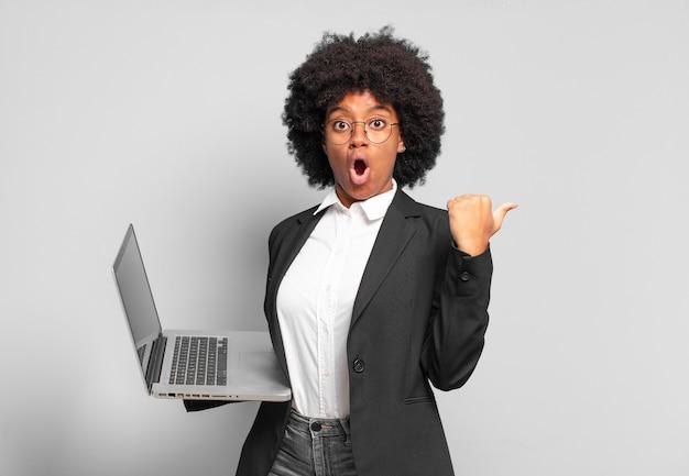 Jonge afro-zakenvrouw kijkt verbaasd van ongeloof, wijst naar een voorwerp aan de zijkant en zegt wow, ongelooflijk. bedrijfsconcept