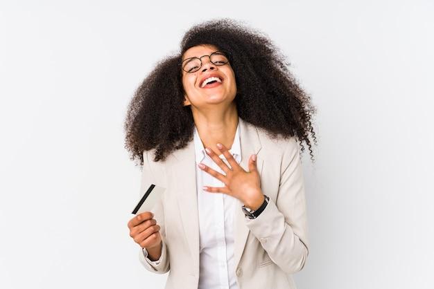 Jonge afro zakenvrouw met een creditcard geïsoleerd jonge afro zakenvrouw met een krediet carlaughs hardop hand op de borst te houden.