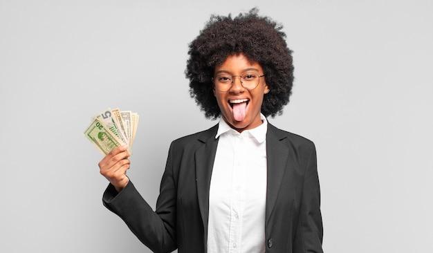 Jonge afro zakenvrouw met vrolijke, zorgeloze, rebelse houding, grappen maken en tong uitsteken, plezier maken. bedrijfsconcept