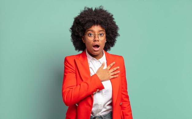 Jonge afro zakenvrouw tegen groene muur