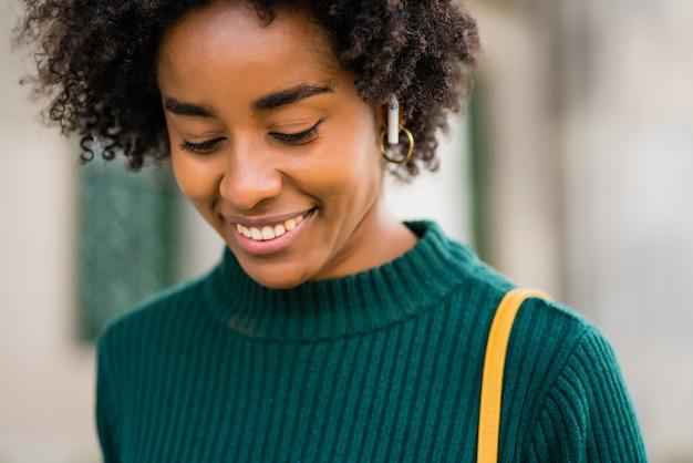 Jonge afroman die naar muziek luistert met zijn mobiele telefoon