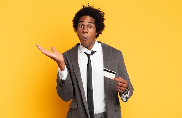 Jonge afroman die verbaasd en geschokt kijkt, met open mond een voorwerp met een open hand aan de zijkant