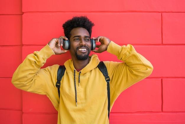 Jonge afromens die aan muziek met hoofdtelefoons luistert.