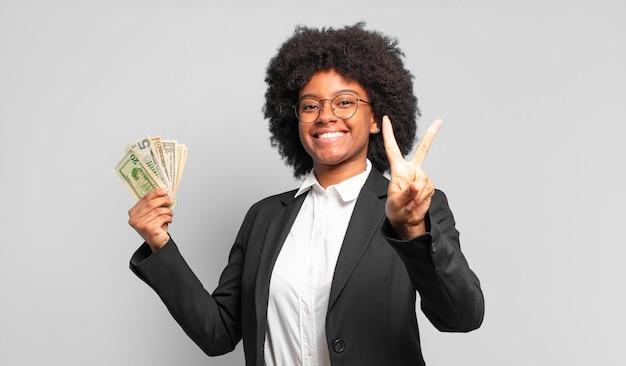 Jonge afroonderneemster die gelukkig, zorgeloos en positief glimlacht en kijkt, overwinning of vrede met één hand gebaart. bedrijfsconcept