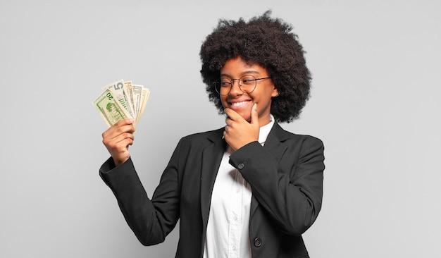 Jonge afroonderneemster die met een gelukkige, zelfverzekerde uitdrukking met hand op kin glimlacht, zich afvraagt en naar de kant kijkt. bedrijfsconcept