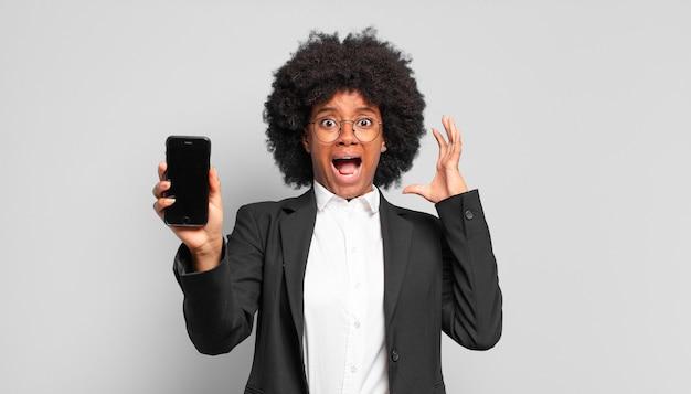 Jonge afroonderneemster die met handen in de lucht schreeuwt, zich woedend, gefrustreerd, gestrest en boos voelt