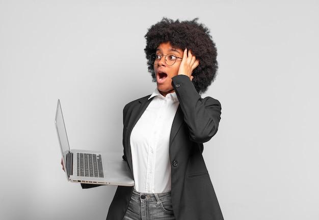 Jonge afroonderneemster die zich blij, opgewonden en verrast voelt, opzij kijkt met beide handen op het gezicht. bedrijfsconcept