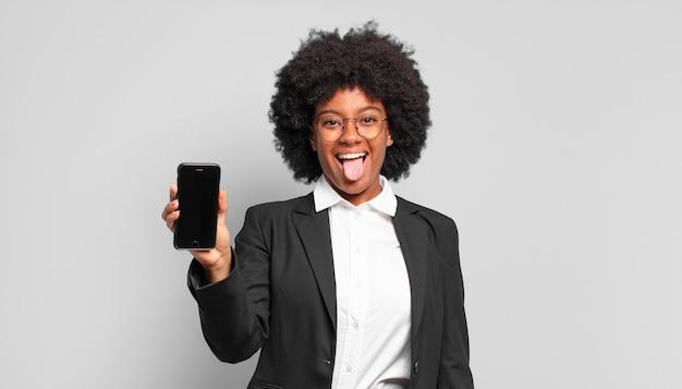 Jonge afroonderneemster met vrolijke, zorgeloze, rebelse houding, grappen maken en tong uitsteken, plezier maken. bedrijfsconcept