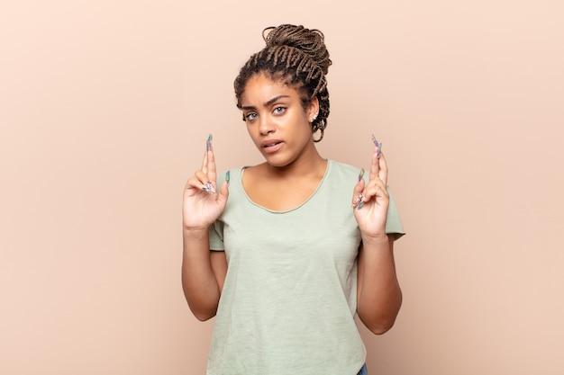 Jonge afrovrouw die angstig vingers kruist en op geluk hoopt met een bezorgde blik