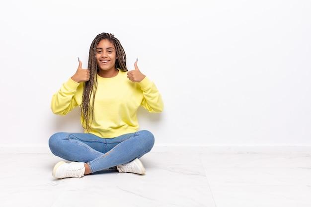 Jonge afrovrouw die breed kijkt gelukkig, positief, zelfverzekerd en succesvol, met beide duimen omhoog