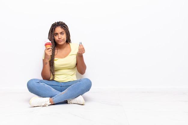 Jonge afrovrouw die capice of geldgebaar maakt