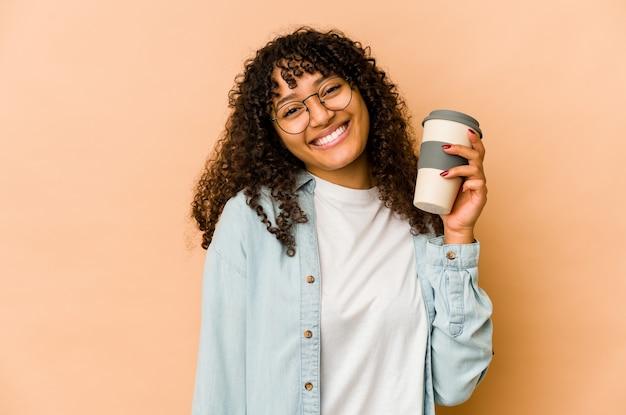 Jonge afrovrouw die een afhaalkoffie gelukkig, glimlachend en vrolijk houdt