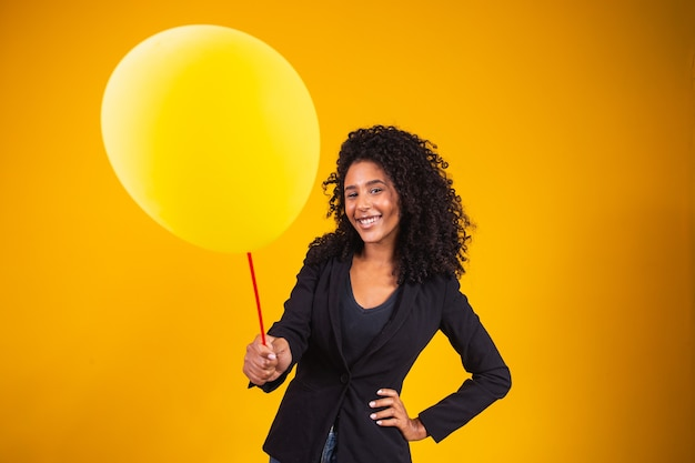 Jonge afrovrouw die een ballon met vrije ruimte voor tekst houdt.