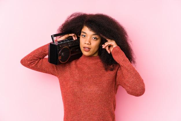 Jonge afrovrouw die een cassete richtende tempel met vinger houdt