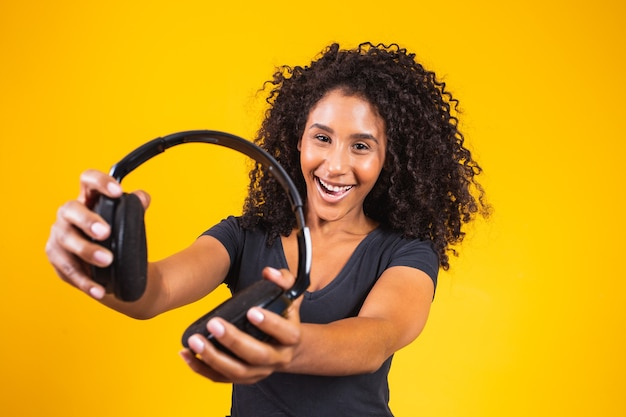 Jonge afrovrouw die een hoofdtelefoon op gele achtergrond houdt. muziek- en entertainmentconcept