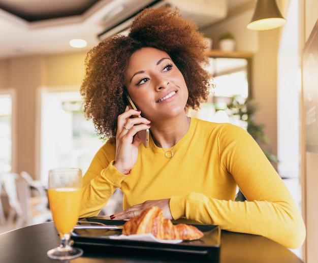 Jonge afrovrouw die een ontbijt heeft, een croissant eet en een jus d'orange drinkt.